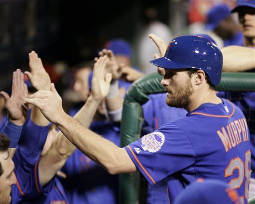 New York Mets' Daniel Murphy returns to high-fives in the dugout after scoring on an single to center by Lucas Duda in the third inning of a baseball game with the Philadelphia Phillies, Monday, April 8, 2013, in Philadelphia. (AP Photo/Tom Mihalek)