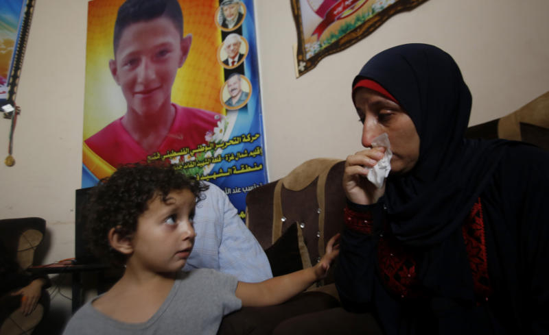 In this Tuesday July 2, 2019 photo, Raeda, mother of 14-year-old Mohammed Ayyoub, sits near a poster with his photo, at the family home in Jabaliya refugee camp. Mohammed was killed during a protest on the fence separating Israel and Gaza in 2018. The Israeli military has opened investigations into 24 potentially criminal shootings of Palestinians in the West Bank and Gaza Strip, but none have yielded indictments and rights groups say little effort is made to gather evidence or interview witnesses. (AP Photo/Hatem Moussa)
