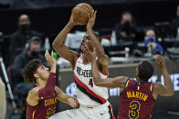 Portland Trail Blazers' Harry Giles III (4) drives to the basket against Cleveland Cavaliers' Brodric Thomas (33) and Jeremiah Martin (3) during the second half of an NBA basketball game, Wednesday, May 5, 2021, in Cleveland. Portland won 141-105. (AP Photo/Tony Dejak)