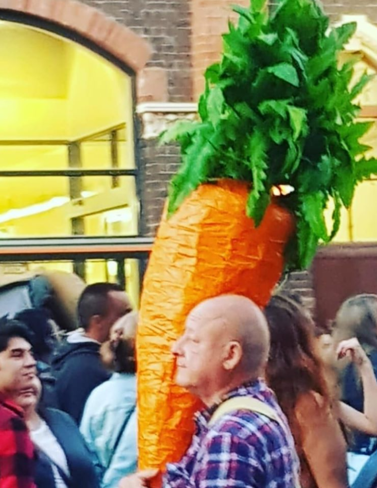 """Photo of """"carrot man"""" Nathan with his giant vegetable in Melbourne."""