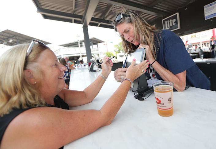 Debbie Bartolome pays for her beer via a cashless system with the help of Summerfest employee Tori Schutz on the first day of Summerfest 2021.