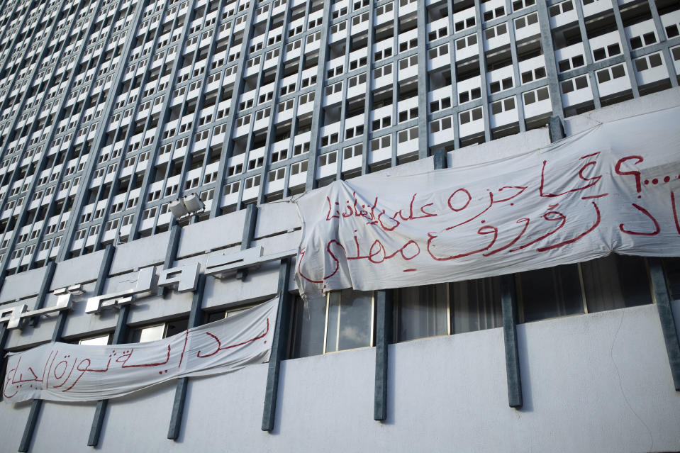 "Banners are hung on a building in Tunis' landmark Avenue Habib Bourgiba, where massive protests took place in 2011, on the tenth anniversary of the uprising , in Tunis, Thursday, Jan. 14, 2021. Banners read ""The uprising of the poor begins"" Tunisia is commemorating the 10th anniversary since the flight into exile of its iron-fisted leader, Zine El Abidine Ben Ali, pushed from power in a popular revolt that foreshadowed the so-called Arab Spring. But there will be no festive celebrations Thursday marking the revolution in this North African nation, ordered into lockdown to contain the coronavirus. (AP Photo/Mosa'ab Elshamy)"