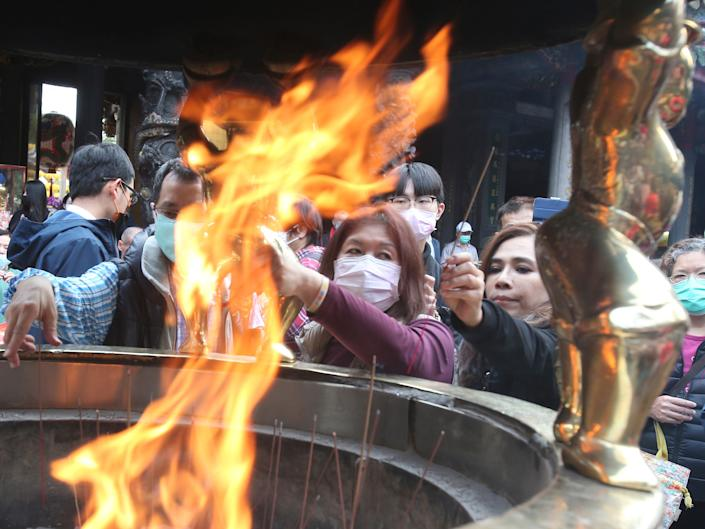 People wear face masks to protect against the spread of the coronavirus as they pray at the popular Longshan Temple in Taipei, Taiwan, Thursday, March 12, 2020. (AP Photo   Chiang Ying ying)