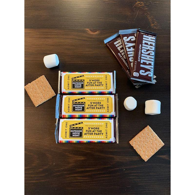 """<p>Wrap this printable around a Hershey's bar, and gift to each guest as their """"ticket."""" Later in the night, every one can use their ticket to create a tasty treat. <br></p><p><em><a href=""""https://hmg-prod.s3.amazonaws.com/files/movienightcandywrappernew-1594047127.pdf"""" rel=""""nofollow noopener"""" target=""""_blank"""" data-ylk=""""slk:Get the Admit One Ticket printable"""" class=""""link rapid-noclick-resp"""">Get the Admit One Ticket printable</a>.</em></p><p><strong>What You'll Need: </strong><a href=""""https://www.amazon.com/Hersheys-Chocolate-Candy-1-55-Oz-Count/dp/B086LHQHLT?tag=syn-yahoo-20&ascsubtag=%5Bartid%7C10070.g.33216073%5Bsrc%7Cyahoo-us"""" rel=""""nofollow noopener"""" target=""""_blank"""" data-ylk=""""slk:Hershey's bars"""" class=""""link rapid-noclick-resp"""">Hershey's bars</a> ($37 for 36 bars, Amazon)</p>"""