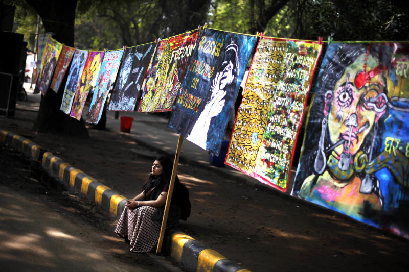 A woman participant sits under paintings as women's groups gather near Indian parliament to protest a new sexual violence law as the parliament convenes in New Delhi, India, Thursday, Feb. 21, 2013. Activists said the law is inadequate and it only partially followed the recommendations of a government panel set up after the fatal gang rape of a woman in New Delhi which led to nation-wide protests. (AP Photo/Altaf Qadri)