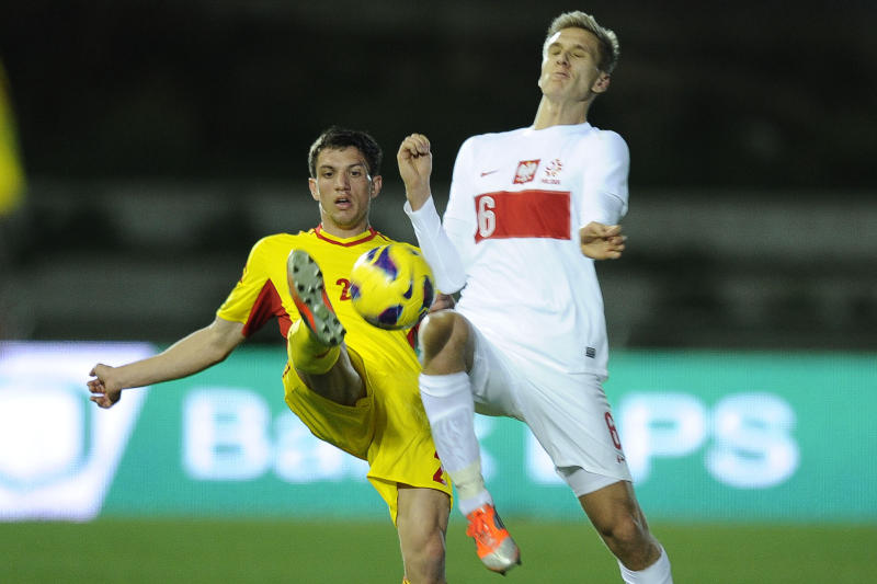 Romania's Constantin Nica vies with Poland's Lukasz Teodorczyk (right) during the friendly football match Poland vs Romania at Ciudad de Malaga stadium in Malaga on February 2, 2013