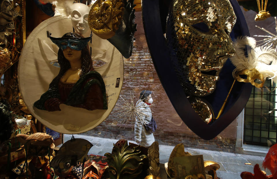 A woman wearing a sanitary mask walks next to a carnival masks shop in Venice, Italy, Saturday, Jan. 30, 2021. Carnival should have begun on Saturday, but the COVID-19 pandemic has made that annual appointment of days of merry-making impossible. (AP Photo/Antonio Calanni)