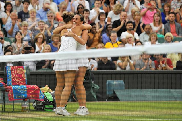Italy's Sara Errani (L) and Roberta Vinci celebrate on match point winning their women's doubles final match against Hungary's Timea Babos and France's Kristina Mladenovic on day 12 of the 2014 Wimbledon Championships in Wimbledon on July 5, 2014 (AFP Photo/Glyn Kirk)
