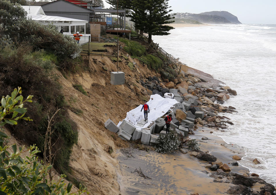 Concrete blocks are craned onto the beach to stop coastal erosion next to houses at Wamberal Beach, on the NSW Central Coast, Saturday, July 18, 2020.