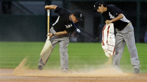 Chicago White Sox grounds crew members spread a drying agent on the infield during the seventh inning of a baseball game between the White Sox and the Seattle Mariners, Sunday, Aug. 26, 2012, in Chicago. (AP Photo/John Smierciak)