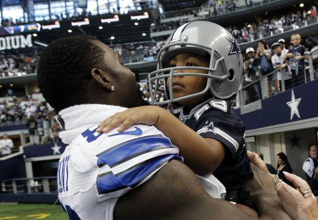 Dallas Cowboys wide receiver Dez Bryant holds his son, Dez Bryant Jr. after the Cowboys beat the St. Louis Rams in their NFL football game in Arlington, Texas September 22, 2013. REUTERS/Mike Stone (UNITED STATES - Tags: SPORT FOOTBALL)
