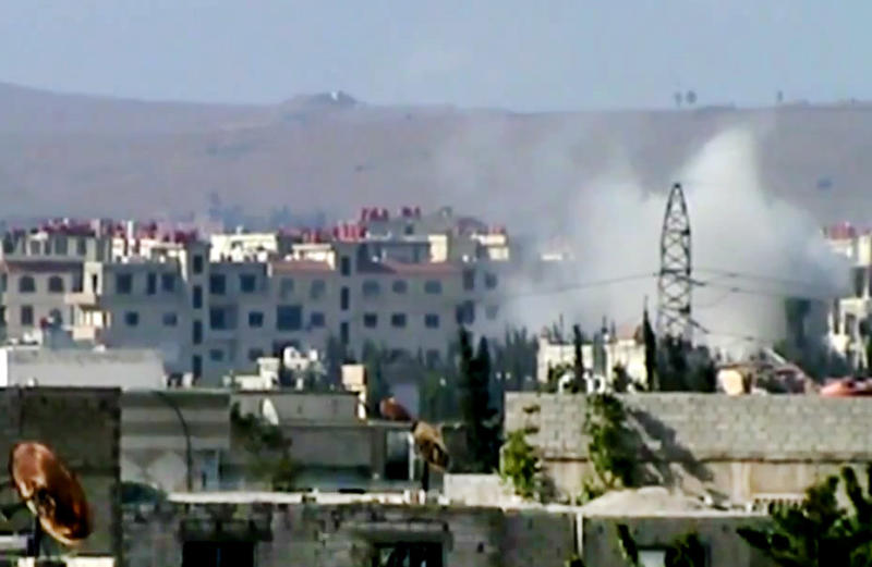 In this image taken from video obtained from the Shaam News Network, which has been authenticated based on its contents and other AP reporting, smoke rises from buildings due to shelling in Damascus, Syria, on Thursday, June 20, 2013. (AP Photo/Shaam News Network via AP video)