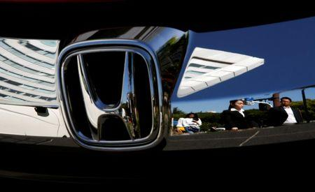 People are reflected on a Honda Motor car outside the company's showroom in Tokyo