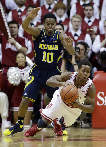 Indiana guard Yogi Ferrell, right, slips under pressure from Michigan guard Derrick Walton Jr. in the first half of an NCAA college basketball game in Bloomington, Ind., Sunday, Feb. 2, 2014. (AP Photo/Michael Conroy)