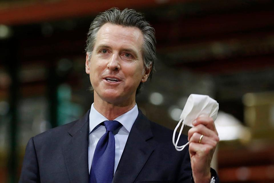 California Gov. Gavin Newsom holds a face mask as he urges people to wear them to fight the spread of the coronavirus during a news conference in Rancho Cordova, Calif.