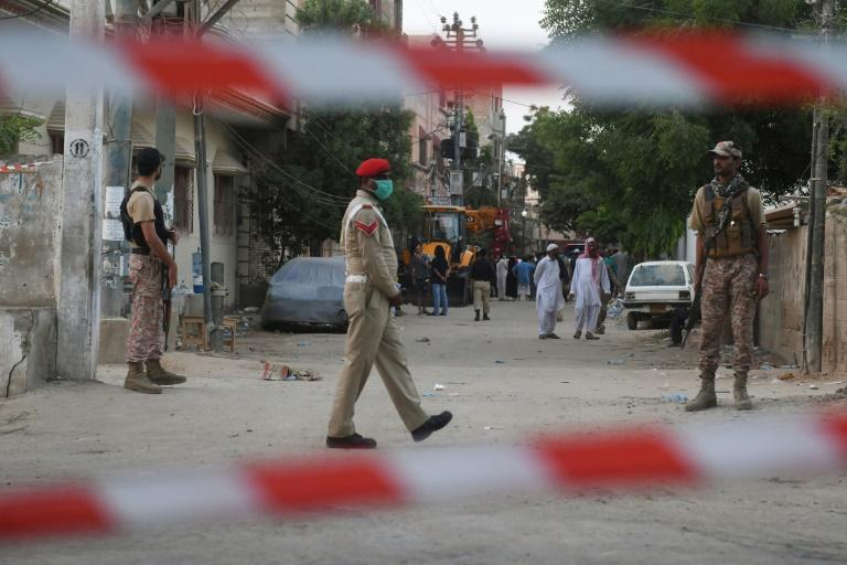 Security personnel patrol a street near the plane crash site in Karachi