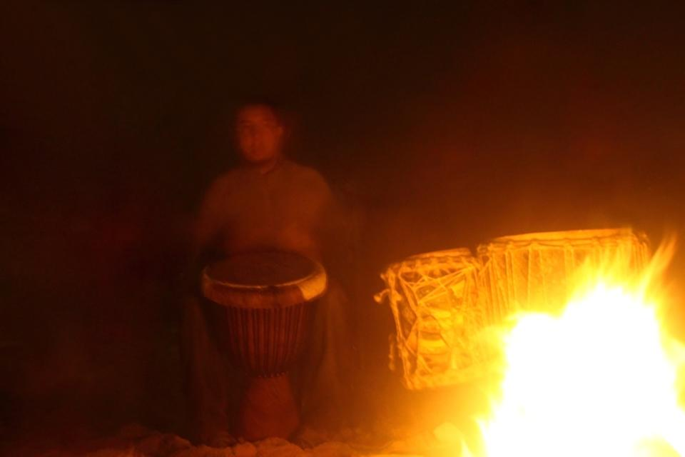 Drummer playing percussion in camp fire at night.