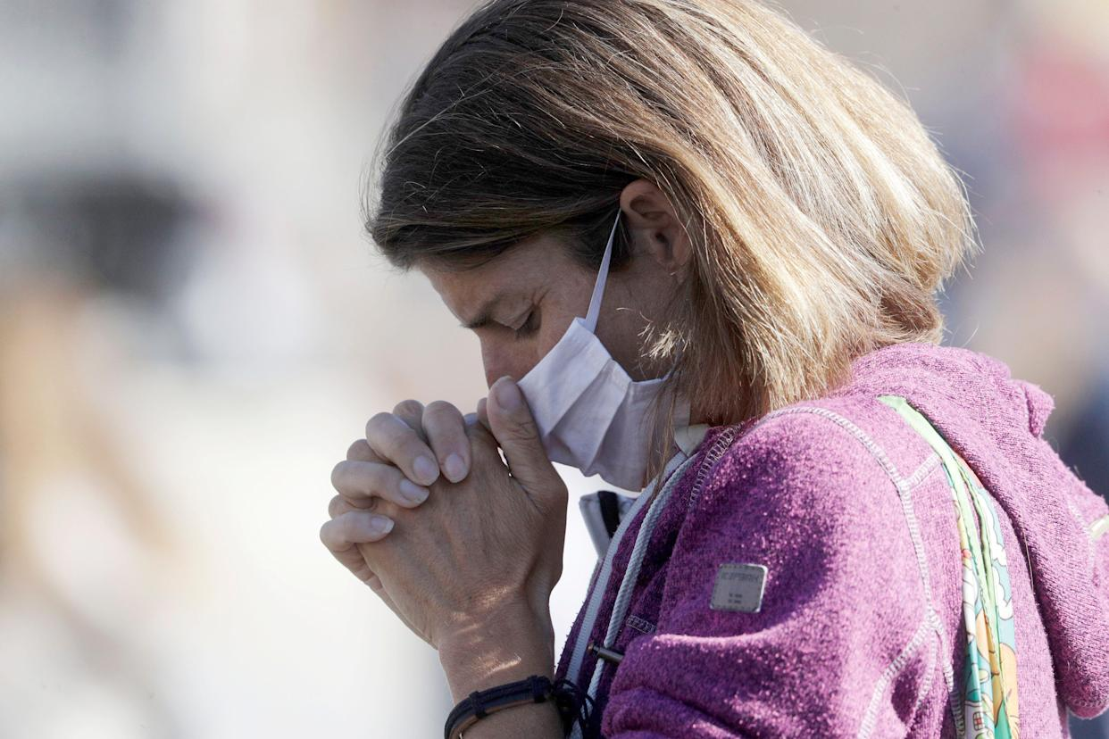 A woman wearing a face mask to curb the spread of COVID-19 holds her hands as she prays during Pope Francis' Angelus noon prayer in St. Peter's Square at the Vatican, Sunday, Oct. 18, 2020.