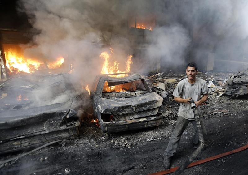 In this picture taken on Thursday August 15, 2013, A Lebanese citizen stand next to burned cars and shops at the site of a car bomb explosion, in an overwhelmingly Shiite area and stronghold of the Lebanese militant group Hezbollah, at the southern suburb of Beirut, Lebanon. Car bombings and rocket attacks targeting Hezbollah strongholds south of Beirut have shaken the militant group and its Shiite supporters to the core, bringing a sense of fear and unease to a community that has been largely spared the violence plaguing the rest of the country. (AP Photo/Hussein Malla)