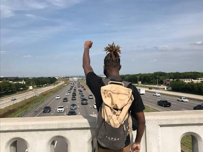 A protester raises a fist in the air on a bridge overlooking Interstate 20 in Arlington, Texas, on June 1, 2020.