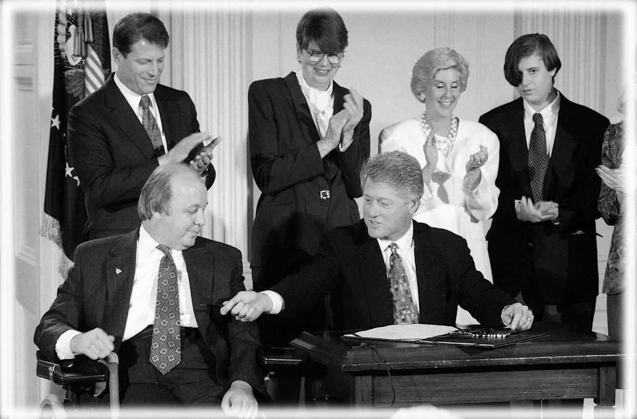 President Bill Clinton hands James Brady a pen after signing the Brady Bill in the East Room of the White House, Nov. 30, 1993. (Photo: Marcy Nighswander/AP, digitally enhanced by Yahoo News)