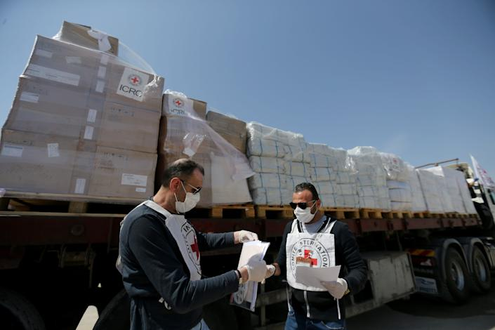 Palestinian workers check medical equipment donated by the International Committee of the Red Cross (ICRC) amid concerns about the spread of the coronavirus disease (COVID-19), at Kerem Shalom crossing in the southern Gaza Strip April 21, 2020.  REUTERS/Ibraheem Abu Mustafa