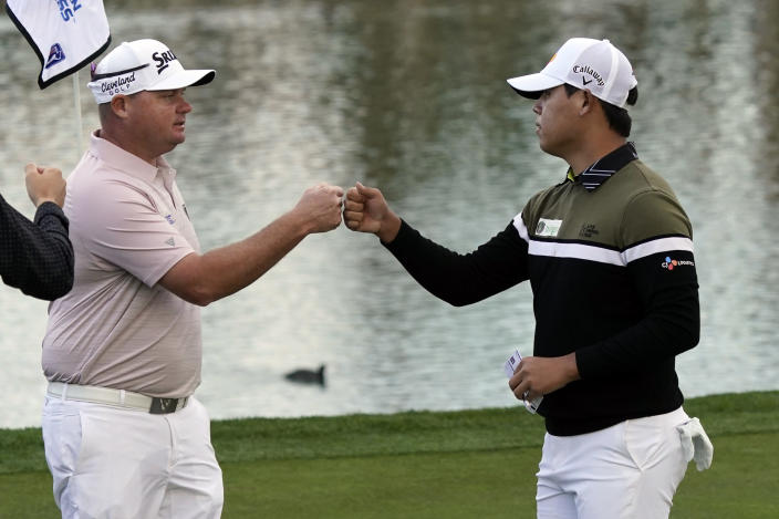 Si Woo Kim, right, bumps fists with Ted Potter Jr. after they finished the second round of The American Express golf tournament on the Nicklaus Tournament Course at PGA West, Friday, Jan. 22, 2021, in La Quinta, Calif. (AP Photo/Marcio Jose Sanchez)