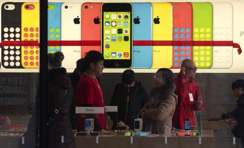 A woman talks to a salesperson in front of an advertisement for iPhones at Apple's retail store in Beijing Monday, Dec. 16, 2013. Apple Inc. might have a chance to pep up cooling iPhone sales in China if it finally can reach a deal with the world's biggest phone carrier. (AP Photo/Ng Han Guan)