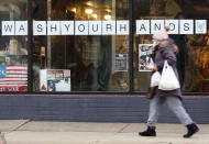 "In this March 19, 2020, photo, a woman in a face mask walks past a ""Wash Your Hands"" sign after buying groceries in Oak Park, Ill., before a two-week ""shelter in place"" order goes into effect. Leaders in the Chicago suburb were the first in the state to take the step, requiring non-essential businesses to close, to try to curb the spread of the coronavirus. (AP Photo/Martha Irvine)"