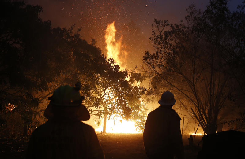 Pictured are firefighters battling a blaze near the Pacific Highway, north of Nabiac in the Mid North Coast region of NSW. Source: AAP