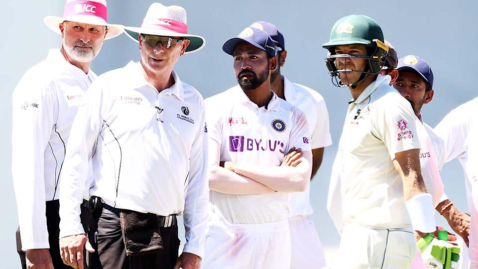 Umpires Paul Reiffel and Paul Wilson, Mohammed Siraj and Tim Paine, pictured here look at the crowd during a suspension in play at the SCG.