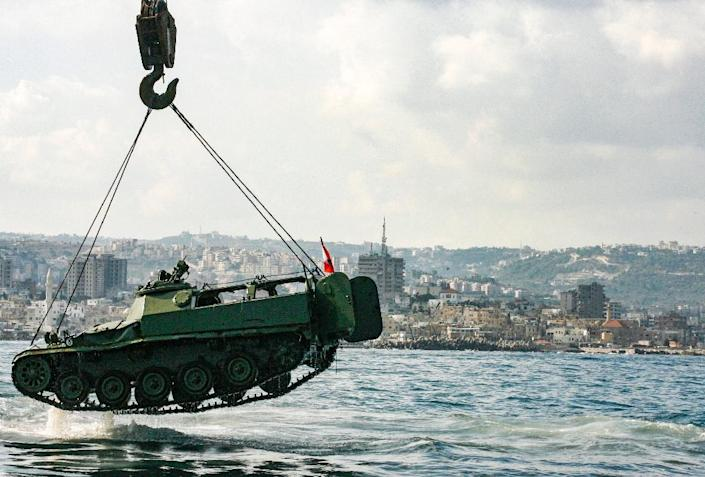 Environmental activists drop off an old mechanised armoured personnel carrier provided by the Lebanese Armed Forces into the Mediterranean Sea, about three kilometres off the coast of the southern Lebanese port city of Sidon, on July 28, 2018 (AFP Photo/Mahmoud ZAYYAT)