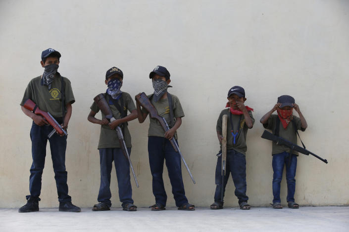 """Children hold their training weapons, some real and some fake, during a display for the media designed to attract the federal government's attention to the dangers of organized crime their town negotiates daily in Ayahualtempa, Guerrero state, Mexico, Wednesday, April 28, 2021. International organizations have condemned the """"recruitment"""" of children and warned of the effects. (AP Photo/Marco Ugarte)"""