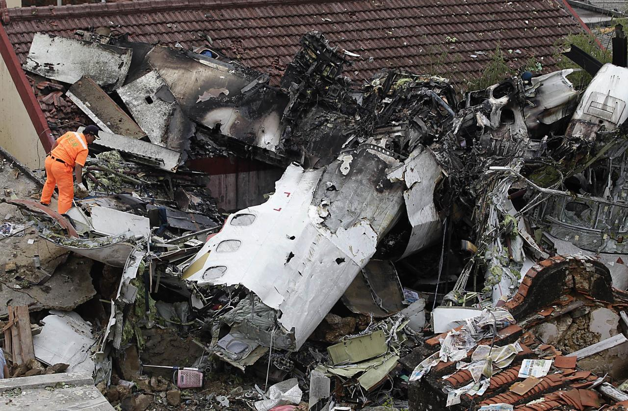 Rescue personnel survey the wreckage of a TransAsia Airways turboprop plane that crashed, on Taiwan's offshore island Penghu July 24, 2014. The leaders of rivals China and Taiwan expressed condolences on Thursday for victims of the plane that crashed during a thunderstorm the previous day killing 48 people including two French nationals. REUTERS/Pichi Chuang (TAIWAN - Tags: ENVIRONMENT TRANSPORT DISASTER TPX IMAGES OF THE DAY)