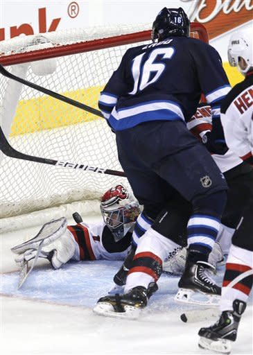Winnipeg Jets' Andrew Ladd (16) scores against New Jersey Devil New Jersey Devils goaltender Johan Hedberg (1) during the third period of an NHL hockey game in Winnipeg, Manitoba, on Thursday, Feb. 28, 2013. (AP Photo/The Canadian Press, John Woods)