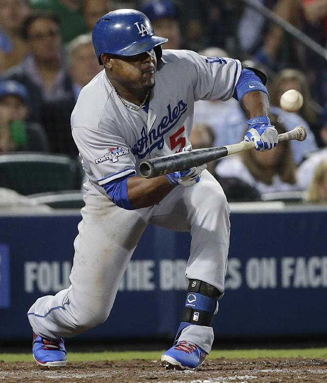 Los Angeles Dodgers third baseman Juan Uribe (5) hits a sacrifice bunt in the fifth inning advancing Adrian Gonzalez to third base and Yasiel Puigto second base against the Atlanta Braves during Game 1 of the National League Division Series, Thursday, Oct. 3, 2013, in Atlanta. (AP Photo/John Bazemore)