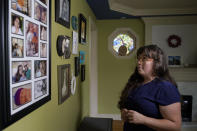 Allison Cullen, of Brockton, Mass., views a wall covered with family photo while speaking with reporters, Thursday, July, 22, 2021, at her home in Brockton. Cullen's husband Flavio Andrade Prado, a Brazilian national Prado is being held by Immigration and Customs Enforcement, or ICE, at the Plymouth County House of Corrections. Cullen, a mother of two, says she and her children haven't been able to visit her husband since before the pandemic. (AP Photo/Steven Senne)