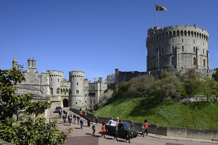 Royal family members walk behind Prince Philip's coffin as it is driven on a modified Land Rover by the Round Tower.
