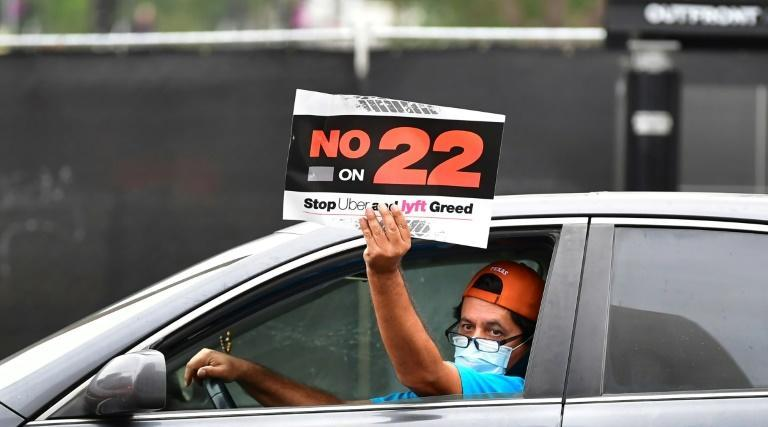 A rideshare driver demonstrates in Los Angeles against Proposition 22, which effectively overturned a state law requiring Uber, Lyft and other app-based, on-demand delivery services to reclassify their drivers and provide employee benefits