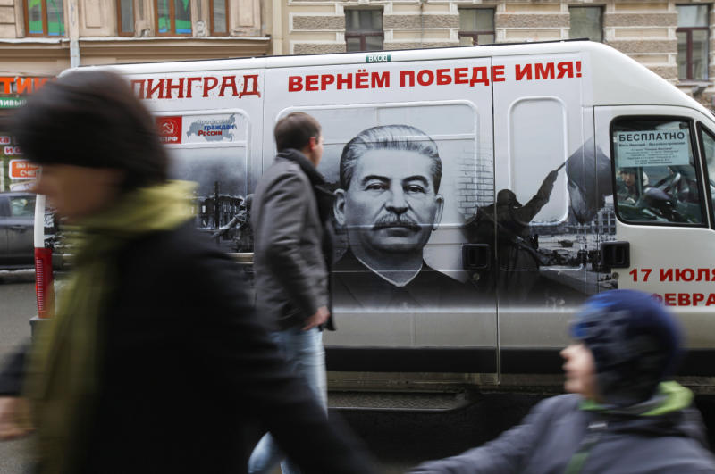 "FILE - In this Saturday, Feb. 2, 2013 file photo people walk by a bus adorned with a portrait of Soviet dictator Josef Stalin and a sign reading ""Stalingrad gets back its victorious name"" in St. Petersburg, Russia. An opinion survey commissioned by the Carnegie Endowment has revealed that Soviet dictator Josef Stalin has remained widely admired in Russia and other ex-Soviet nations despite his repressions that killed millions of people. It has found that support for Stalin in Russia has actually increased since the 1991 collapse of the Soviet Union.(AP Photo/Elena Ignatyeva)"