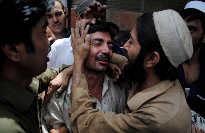 People comfort a family member of a female polio worker who was killed by unknown gunmen, at a local hospital in Peshawar, Pakistan, Tuesday, May 28, 2013. Police say gunmen in Pakistan have shot dead a female polio worker and wounded another in the northwest, police said. (AP Photo/Mohammad Sajjad)
