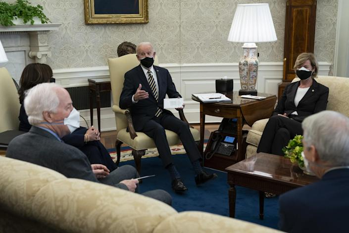 President Biden speaks with lawmakers in the Oval Office.