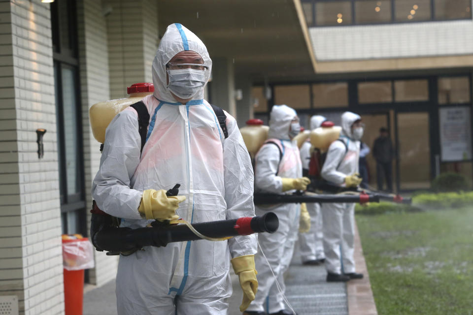 Taiwanese army soldiers wearing protective suits spray disinfectant over a road during a drill to prevent community cluster infection, in New Taipei City, Taiwan, Saturday, March 14, 2020. The city's authorities conducted the drill to simulate the situation before and after community cluster infection of the new coronavirus. The drill's scenario assumes that the COVID-19 had spread within a community of hundreds of people living in buildings. For most people, the new coronavirus causes only mild or moderate symptoms. For some it can cause more severe illness. (AP Photo/Chiang Ying-ying)