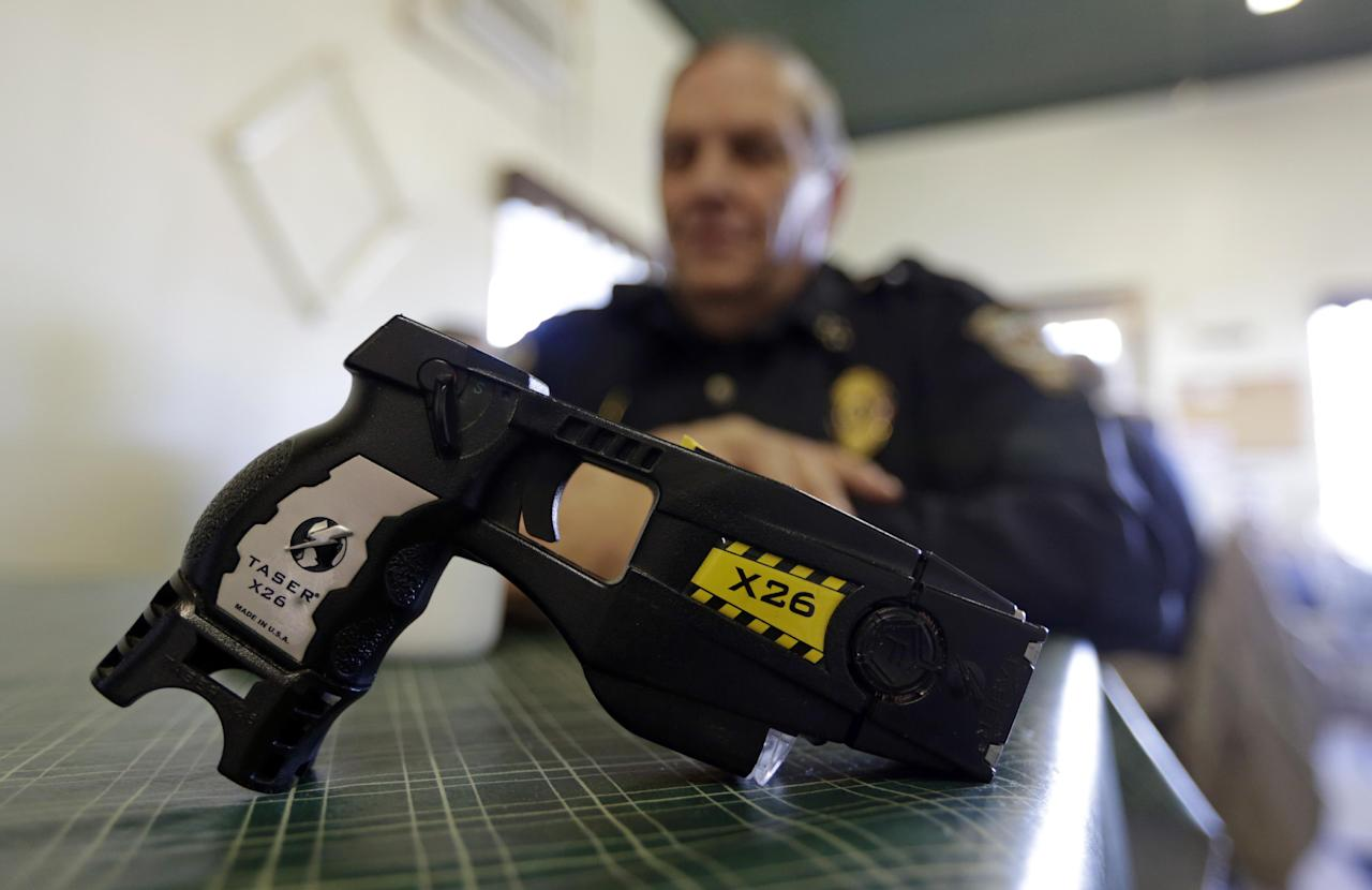 In this Nov. 14, 2013 photo, a Taser X26 is shown as Knightstown Police Chief Danny Baker talks about being shot by the weapon to raise money for his department in Knightstown, Ind. Baker is trying to raise money to lease a new car for the department by agreeing to be shot with his Taser. (AP Photo/Michael Conroy)