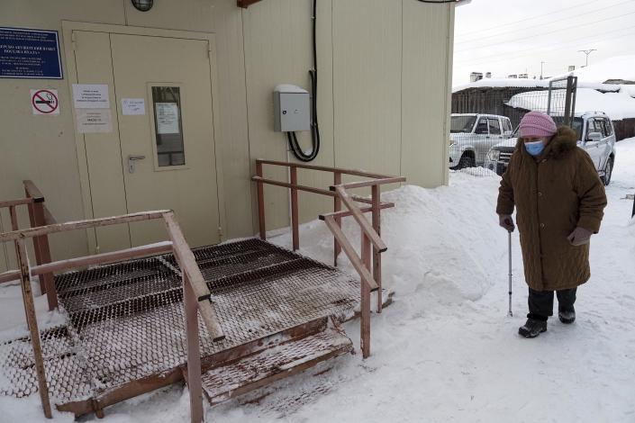 An elderly woman walks to a local rural medical post to get a Sputnik V vaccine in the village of Ikhala in Russia's Karelia region, Tuesday, Feb. 16, 2021. Russia's rollout of its coronavirus vaccine is only now picking up speed in some of its more remote regions, although experts say the campaign is still moving slowly. (AP Photo/Dmitri Lovetsky)