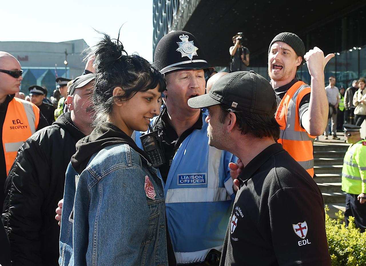 <p>In one of the most viral photos of the year, counter-protester Saffiyah Khan is shown smiling in defiance at a raging English Defence League (EDL) demonstrator in Birmingham. The protest was a response to the Westminster terror attack earlier in the year. (PA) </p>