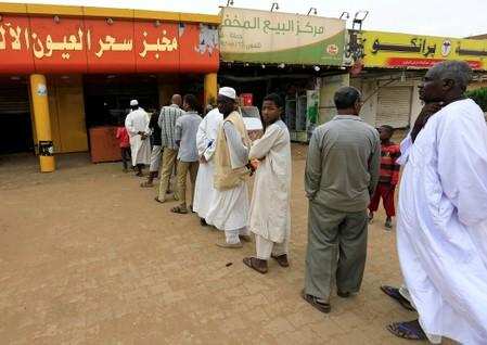 Sudanese civilians stand in a queue to a bakery in Khartoum