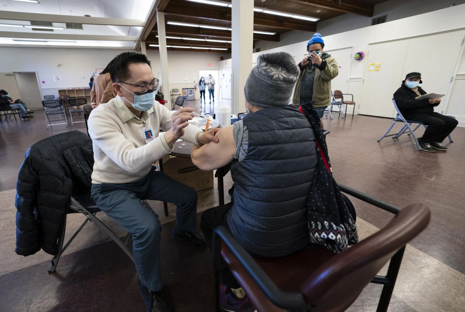 Dr. E. Kwok administers a COVID-19 vaccine to a recipient at a vaccination clinic run by Vancouver Coastal Health, in Richmond, British Columbia, Saturday, April 10, 2021. (Jonathan Hayward/The Canadian Press via AP)