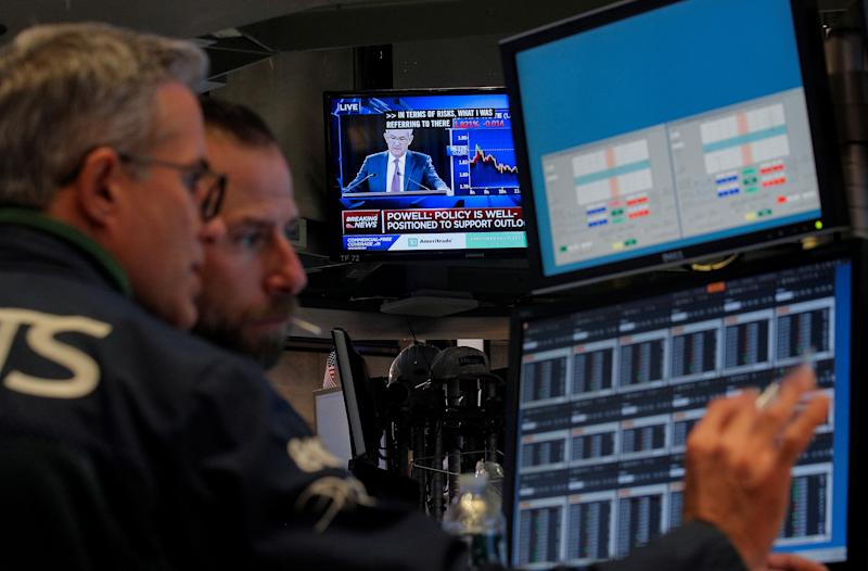 Traders work, as a screen shows Federal Reserve Chairman Jerome Powell's news conference after the U.S. Federal Reserve interest rates announcement, on the floor of the New York Stock Exchange (NYSE) in New York, U.S., October 30, 2019. REUTERS/Brendan McDermid