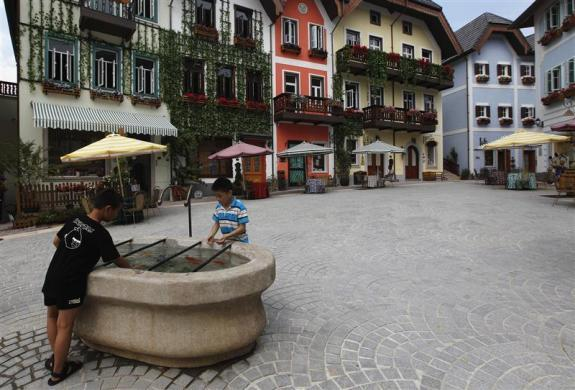 Children play with water in the area of the replica of Austria's UNESCO heritage site, Hallstatt village, in China's southern city of Huizhou in Guangdong province, June 1, 2012.